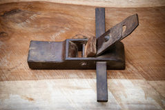 Wood plane tool. An old fashioned wood plane tool on a piece of wood with wood shavings Royalty Free Stock Photo