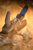Wood Planer. Old wood planer and shavings on wooden background Royalty Free Stock Images
