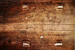 Rustic wood plank. A old wooden plank with nails, staples and little pieces of wood attached to the surface royalty free stock photos