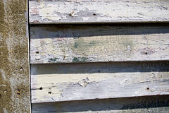 Wood plank lap siding. Aged wood lap siding with paint peeling on an old building Royalty Free Stock Photos