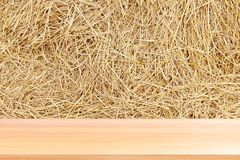 Wood plank on straw, empty wood table floors on straw hay dry background, wood table board empty front straw wall backdrop royalty free stock photo
