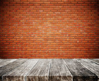 Wood plank tabletop, with defocus brick white wall texture background Stock Image
