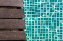 Wood plank and turquoise tile. In swimming pool Royalty Free Stock Image