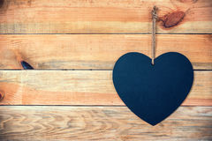 Wood planks with a chalkboard in the shape of a  heart, love greeting card background with copy space Royalty Free Stock Photography