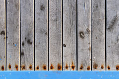 Wood planks with rusted screws texture. Texture of wood planks with rusted screws and a blue rail at the bottom. Suitable for web and print banners and layouts stock photo