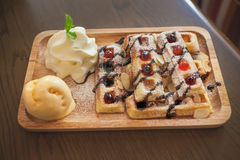 Wood plate of belgian waffles with ice cream and whipped cream Royalty Free Stock Image