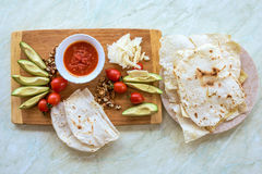 Wood plate with food, on a white table Royalty Free Stock Photo