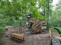 Wood play structure with benches, swings, and dinosaur. Large wood play structure with benches, swings, and dinosaur Stock Images