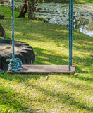 Wood playground swing hanging in green grass field. Royalty Free Stock Photography