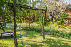 Wood playground swing hanging in green grass field. Stock Image