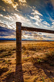 Wood Post Barbed Wire Fence on Prairie. A wood barbed wire fence on the prairie with the Rocky Mountains in the background. The sky is blue and orange with royalty free stock photography