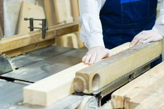 Wood processing. Confident young male carpenter working with wood in his workshop royalty free stock photo