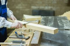Wood processing. Confident young male carpenter working with wood in his workshop stock image