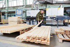 Wood processing manufacture. Worker of wood processing manufacture operating on woodworking machine Stock Photo