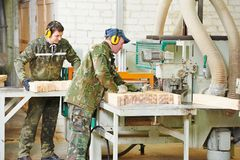 Wood processing manufacture. Workers of woodworking manufacture operating on machine Stock Photo