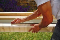 Man`s hands and arms smoothing natural wooden beam using sandpaper while he is working outside. Sanding of wood beams spruce for c stock images
