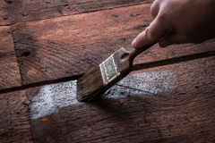 Wood protection with preserver. Painter holding a paintbrush over wooden surface, protecting wood for exterior influences and weathering.  Do-it-yourself concept Stock Images