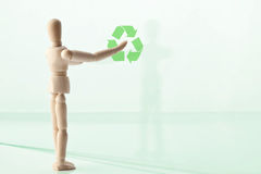 Wood puppet with green recycling symbol Stock Photo