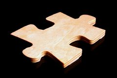 Wood Puzzle Piece. A large wooden puzzle piece on a black surface Royalty Free Stock Photo