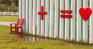 Wood red bench  in front of multi colour wall. Wood red bench  in front of multi color wall and symbol for lovers use for fun Stock Image