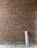 Wood and red brick wall. A red brick wall with wood debris leaning against it Stock Photo