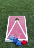 Red and white corn hole board with bean bags royalty free stock photography
