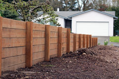 Wood Retaining Wall. Horizontal Wood Retaining Wall, staggered lower as it reaches the street royalty free stock photography