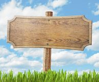 Wood road sign on grass and sky background Royalty Free Stock Images