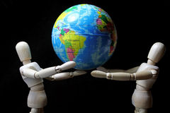 Wood robot hold mini  world in earth day Royalty Free Stock Images