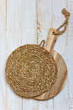 Wood round cutting board and wicker rattan coaster on white plank wood background, rustic kitchen interior Royalty Free Stock Photo