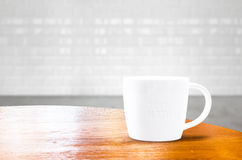Wood round table with white mug at brick tile room Royalty Free Stock Photos