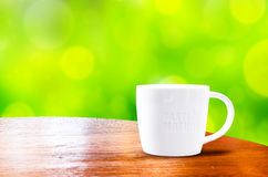 Wood round table with white mug with green bokeh background Stock Photos