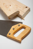 Wood saw and board Stock Image
