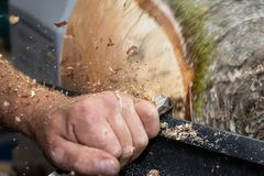 Wood sawdust shavings squirting while creating timber bowl royalty free stock photography