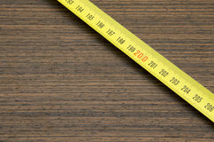Wood. Scale measuring tape on wooden background Royalty Free Stock Photo
