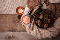 Wood scents for winter time aromatherapy. Pine cones, candles, essential oil bottles, top view. Spa relax winter concept. Copy space stock photography