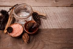 Wood scents for winter time aromatherapy. Pine cones, candles, essential oil bottles, top view. Spa relax winter concept, copy. Space royalty free stock photos