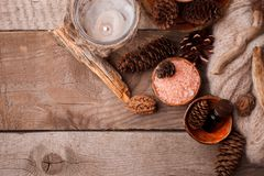 Wood scents for winter time aromatherapy. Pine cones, candles, essential oil bottles, top view. Spa relax winter concept, copy. Space stock image