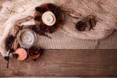 Wood scents for winter time aromatherapy. Pine cones, candles, essential oil bottles, top view. Spa relax winter concept, copy. Space royalty free stock image