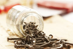 Wood screw. Assoretd wood screw on the wooden surface and overturn jar Stock Image