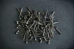 Wood screws on laminated chipboard. Wood screws pile top view Royalty Free Stock Images