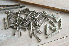 Wood screws and plastic anchors on wooden planks. Wood screws and anchors pile Royalty Free Stock Image