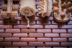 Wood scrubbing brush massagers and loofah on textured wooden pla Royalty Free Stock Photos