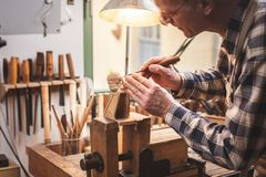 Wood sculptor at a workbench carving a wooden figure stock photo