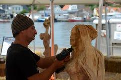 Wood Sculpture Artist. Sonderborg, Denmark - June 22, 2017: International Wood Sculpture Festival 2017, Artists work on theur sculptures with chisels and Stock Photos