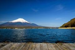 Wood seat to view Mt. Fuji from Yamanaka lake. Wooden bridge seat to see Mountain fuji or Fujisan at Yamanaka lake against blue sky in Yamanashi, Japan. The most Royalty Free Stock Photos