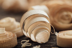 Wood shavings on the carpenter`s workbench. Close up: woodworking and carpentry concept Stock Photos