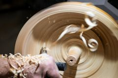 Wood shavings in motion while turnery of a wooden bowl royalty free stock image