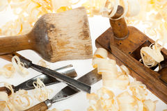 Chisels plane and mallet with wood shavings. Chisels plane and mallet for woodcutter with wood shawings on white background Royalty Free Stock Images