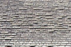 Close up on wood shingle roof in poor repair, falling apart. Wood shingle roof in poor repair. Wood shingles are thin, tapered pieces of wood primarily used to Stock Photo